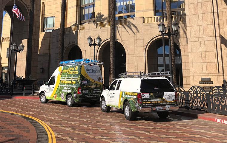 two pestmaster services vehicles parked in front of a commercial building