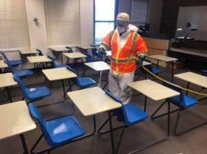 a technician treating a classroom for coronavirus