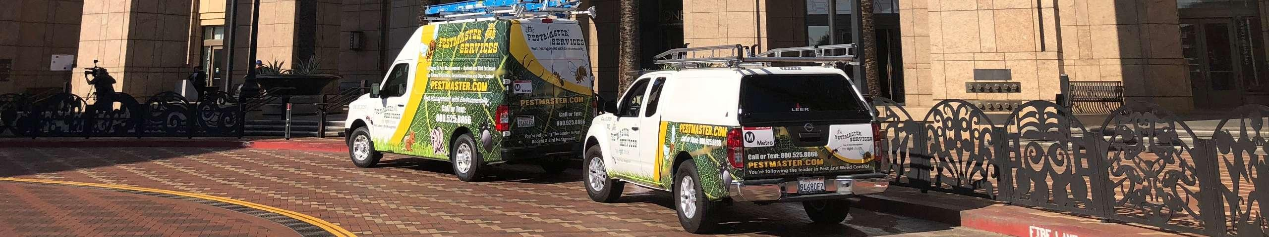 two pest control service vehicles parked outside of a commercial building