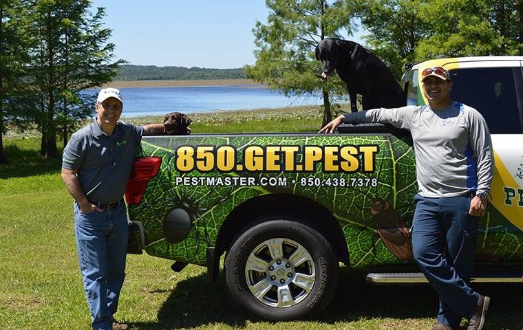 two pest technicians standing by service vehicle with dogs