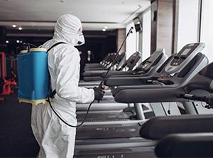 a technician treating treadmills for coronavirus