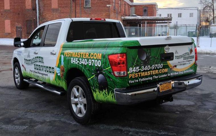 a pestmaster services truck in front of a commercial building