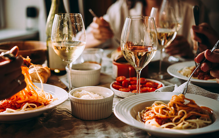 a fancy table in a restaurant with pasta and wine