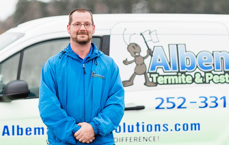 residential and commercial account specialist stands in front of branded vehicle