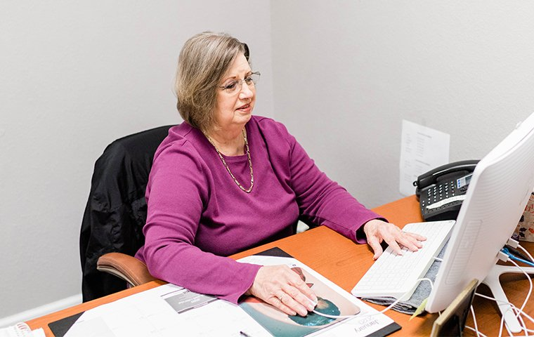 senior customer care specialist sits at desk