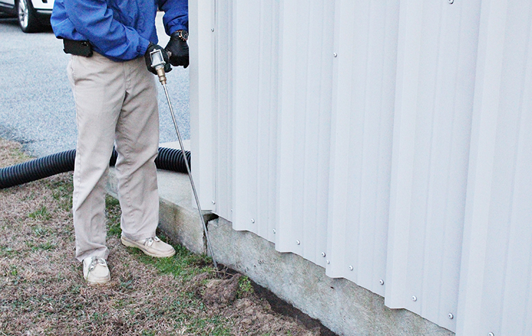 technician treating the perimeter of virginia beach home's foundation for termites
