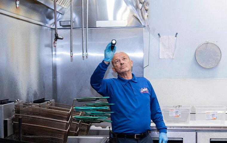 a pest technician inspecting a bryceville florida commercial kitchen