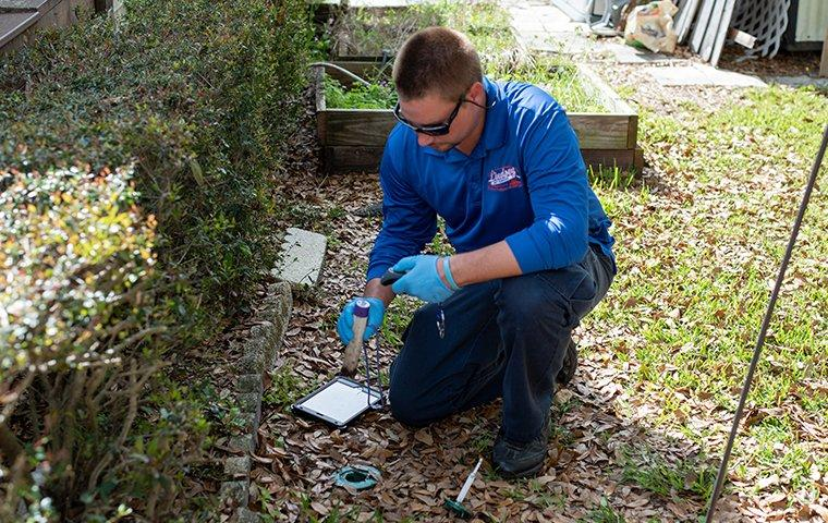 pest control tech inspecting for termites outside a bryceville florida home