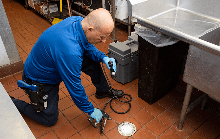 a technician cleaning a drain in and amelia island restaurant