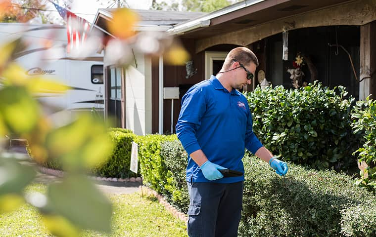 a technician inspecting the exterior of a home in fernandina beach florida