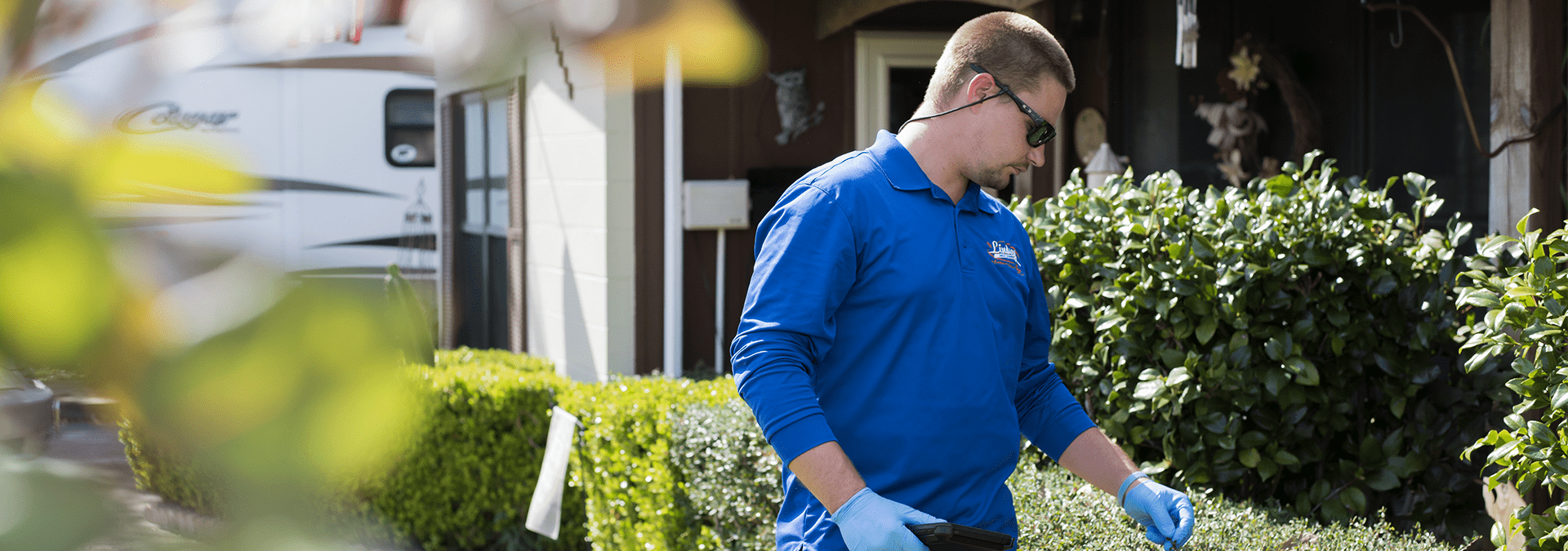 a technician inspecting the shrubs outside of a jacksonville florida home