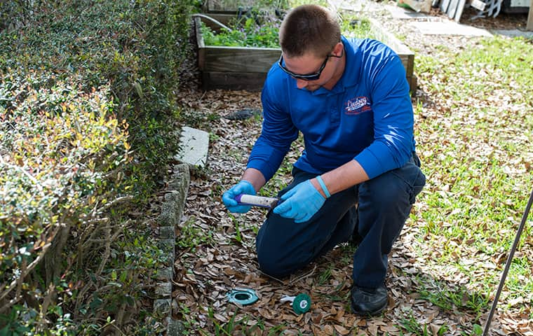 a lindsey pest services technician installing termite control in middleburg florida