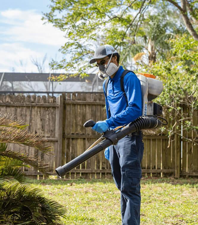 a technician spraying shrubs outside of a jacksonville home for mosquitoes