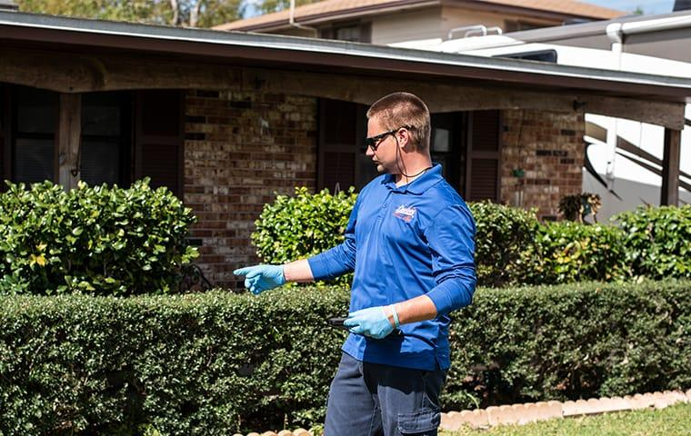 a technician standing in front of and inspecting a palatka florida home for pests