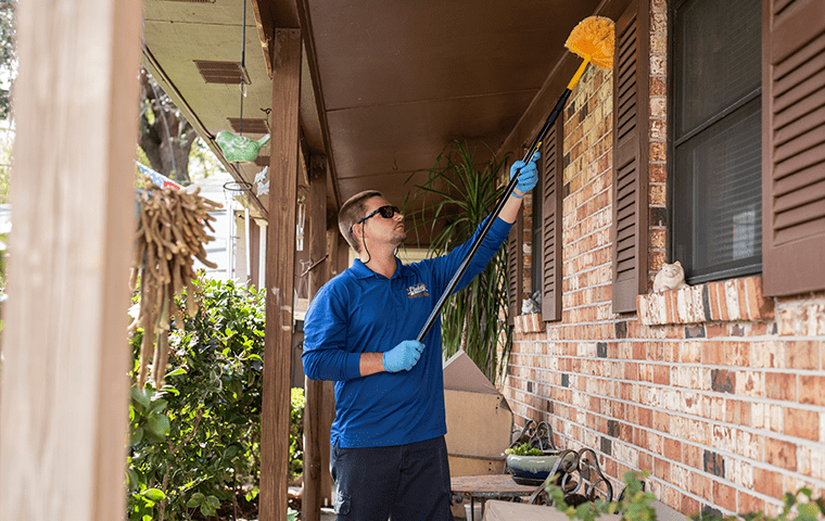 a technician sweeping the outside of a jacksonville beach home
