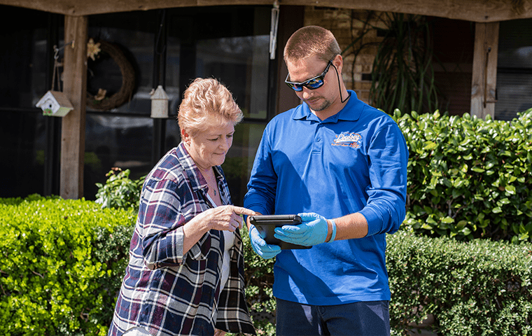 a pest technician going over information with a neptune beach resident