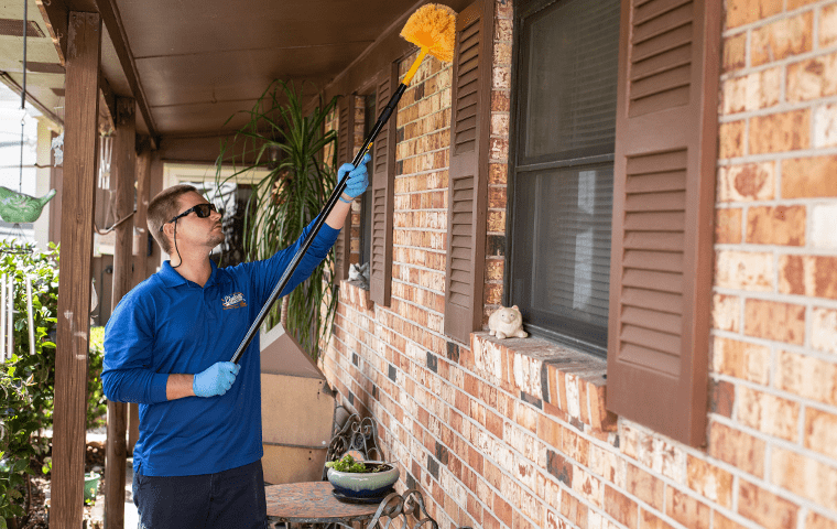 a pest technician dewebbing the outside of a home in ponte vedra beach florida