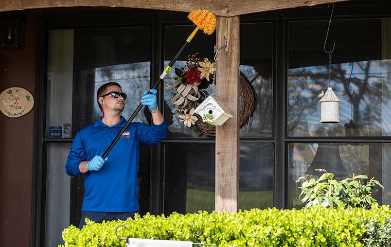 a technician dewebbing an amelia island florida home