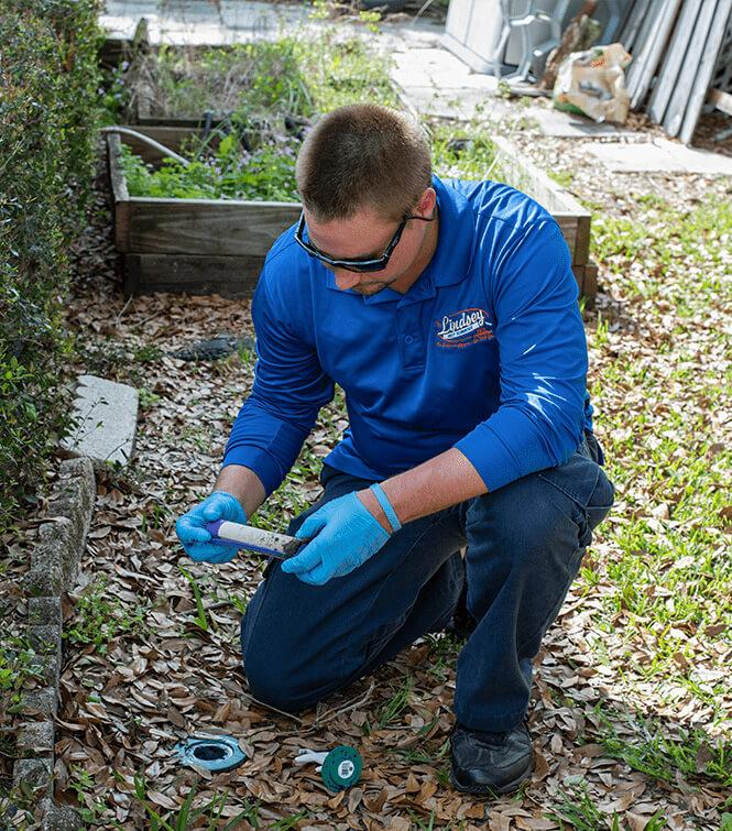 a technician checking a termite baiting trap outside of a jacksonville florida home