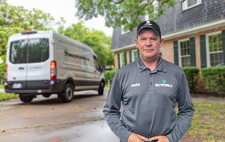 a finally pest control technician standing outside of a house in indianapolis indiana