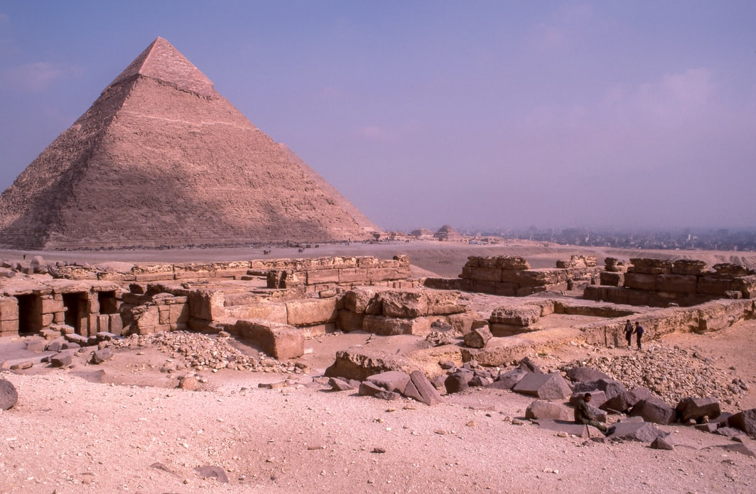 The Great Pyramid in Egypt during the day with ruins scattered in the foreground