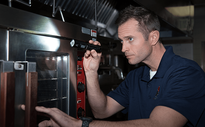 technician inspecting commercial kitchen