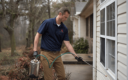pest control technician spraying exterior