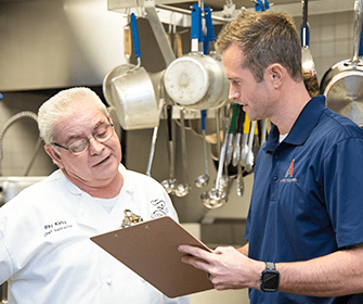 pest control technician talking to chef at restaurant
