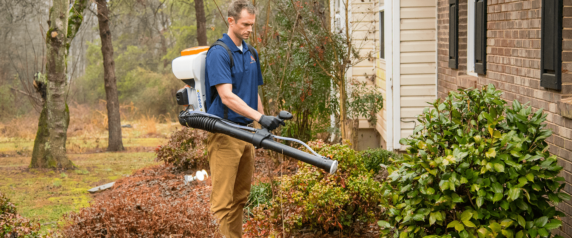 a-1 technician misting shrubs outside of a north carolina home