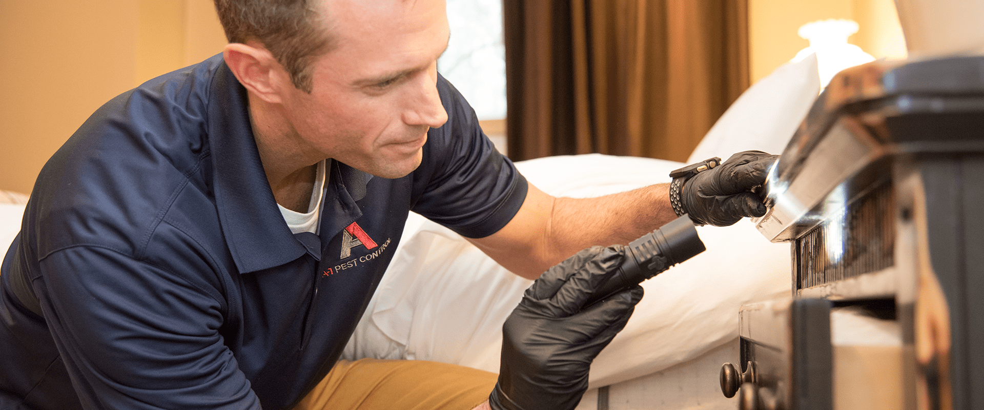 a-1 technician inspecting bedroom furniture for bed bugs
