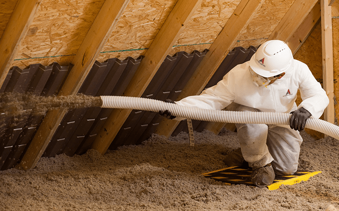 a-1 technician spraying insulation into an attic