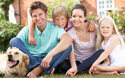 family with pet on lawn
