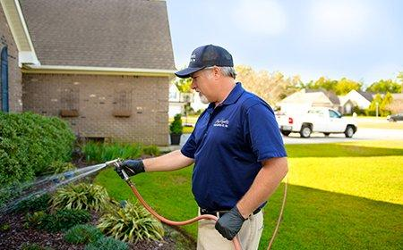 a pest expert treating the exterior of a home