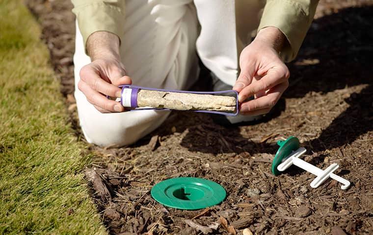 a technician servicing a termite bait station in baltimore