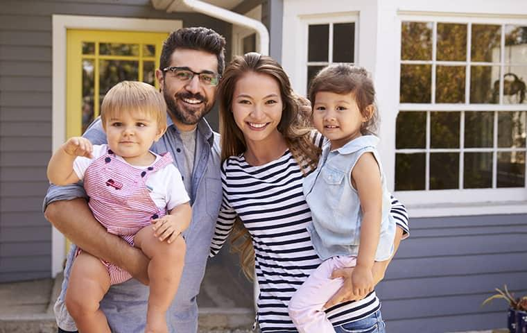 a happy family of four in front of their house in essex