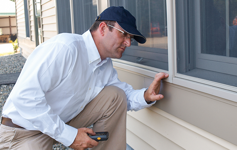 a technician inspecting the exterior of a home in overlea