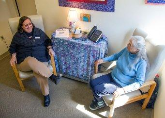 Social worker sitting and talking with an older patient in a counseling room