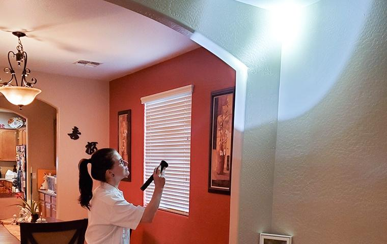 a pest control service technician inspecting the interior of a home for pests