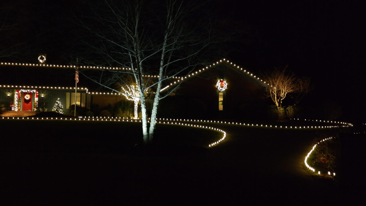 a house with christmas lights lining the driveway