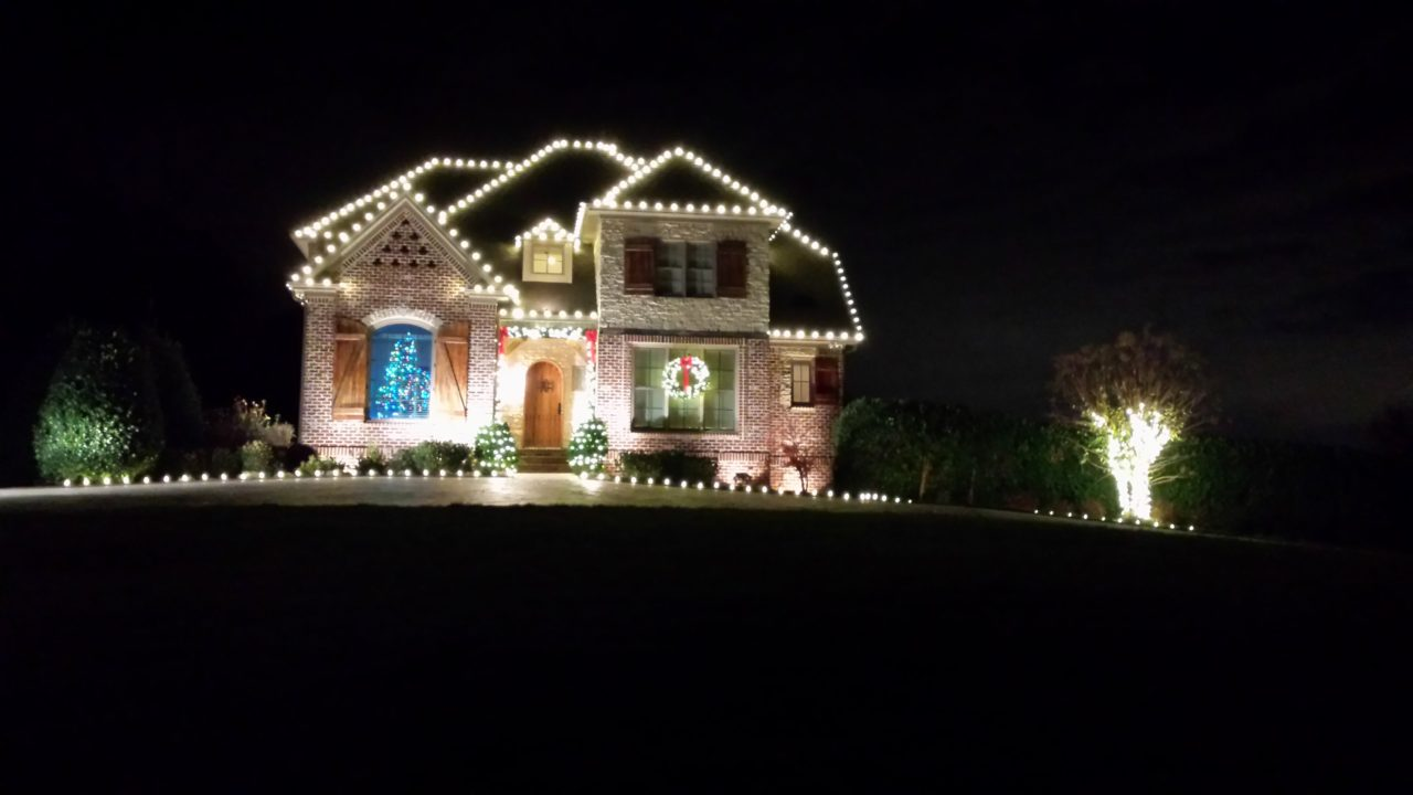 a large brick house with christmas lights