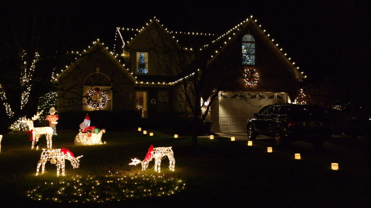 a house and lawn ornaments with christmas lights