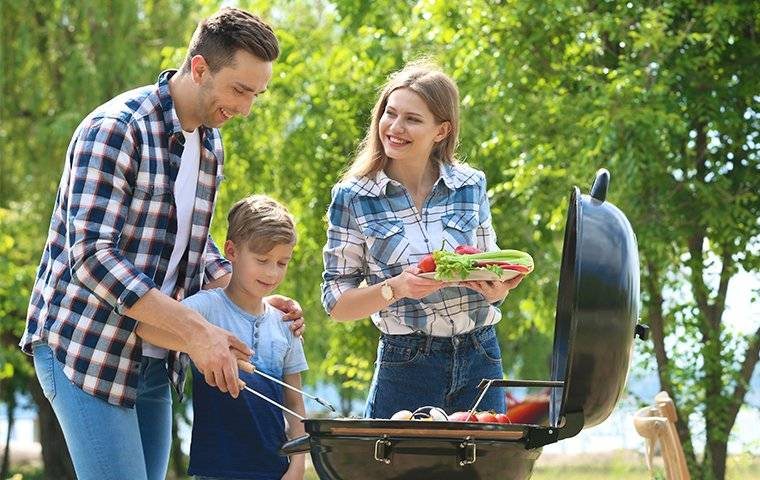 family cooking food on a grill