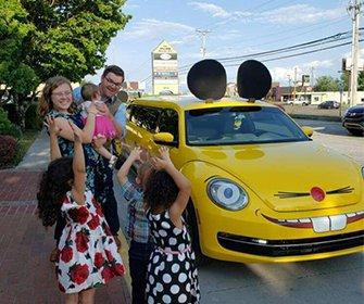 a family standing by the truly nolen mouse car