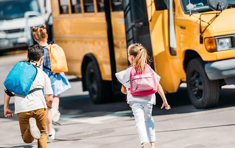 a group of childrn running toward a short yellow school bug unaware of their peers bed bug infestation and the possibility of taking the hitchhiking pest home