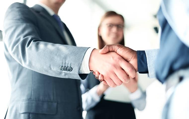 two businessmen shaking hands inside an office in san antonio texas