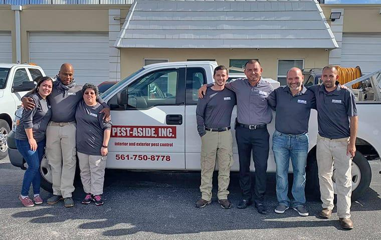 the staff of aaa riteway and pest aside standing in front of a company vehicle in pompano beach florida