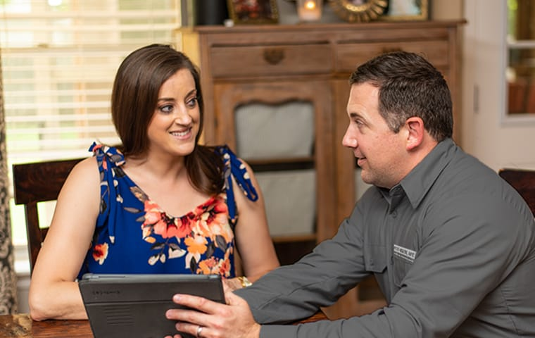 a technician and homeowner sitting at a table using software in boca raton florida