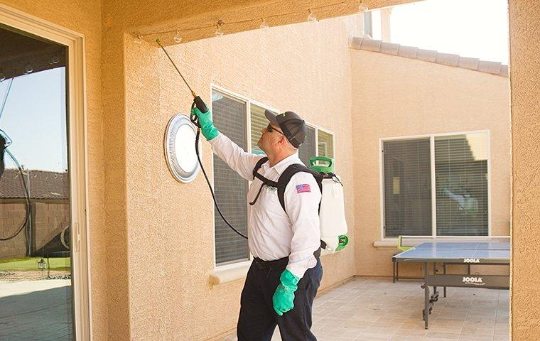 technician doing a spray treatment outside home