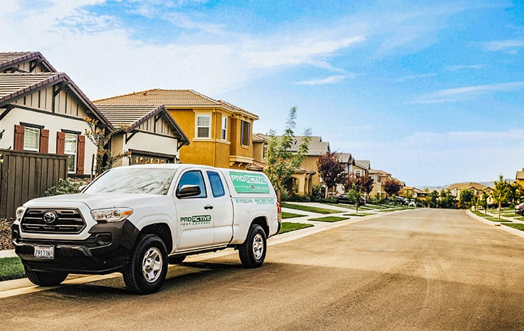 a service truck from pro active pest control sitting in the street in front of homes in woodland california