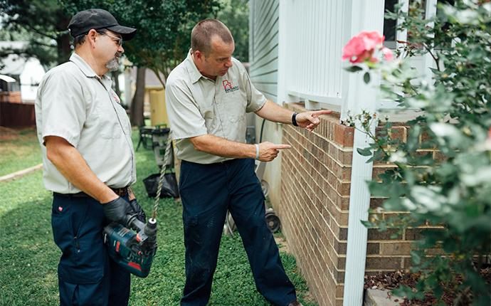technicians inspecting exterior of house